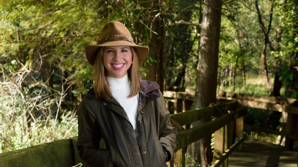 A young woman with brown hair wearing a tan hat with a green jacket and khaki pants leans against a wooden railing.