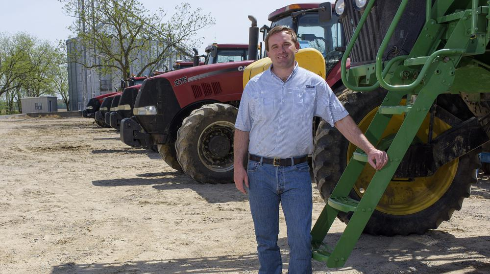 A man wearing a blue collared shirt rests his hand on a green tractor with several red tractors parked behind him.