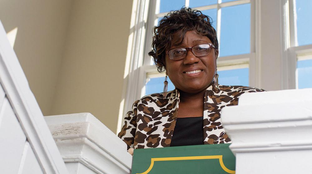 """A woman standing behind a green sign that reads """"Oktibbeha County 4-H."""""""