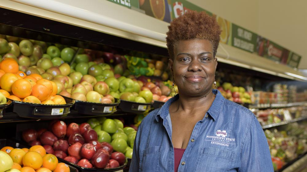 A woman wearing a blue collared jacket stands in the fruit aisle of a grocery store.