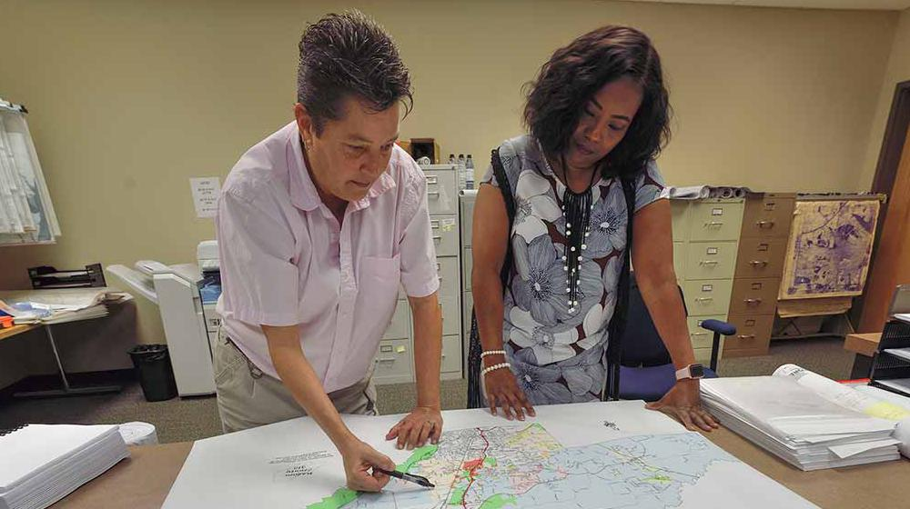 On the left, a woman with short hair and a light pink, collared shirt leans on the table, holding a pen above an area of a map. On the right another woman wearing a blue floral dress leans on the table and looks at it.