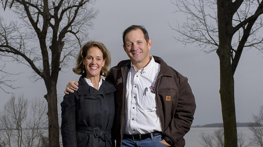 A man stands next to a woman with his arm around her shoulders while they both smile at the camera; a lake rests in the background.