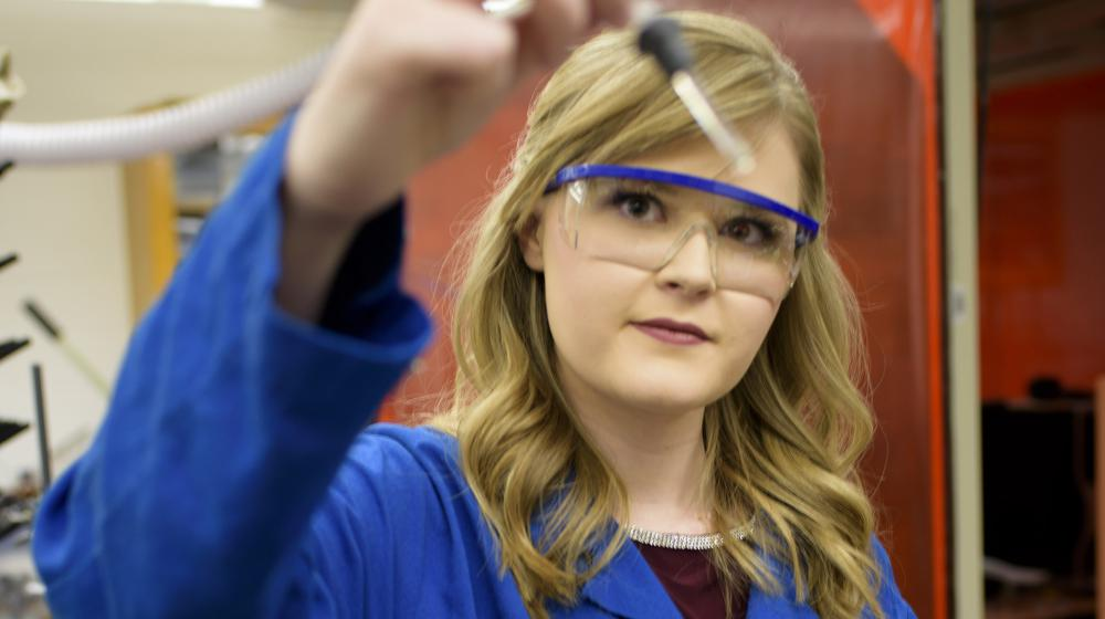 A blonde young woman wearing a blue lab coat and safety glasses holds a glass dropper up to the camera.