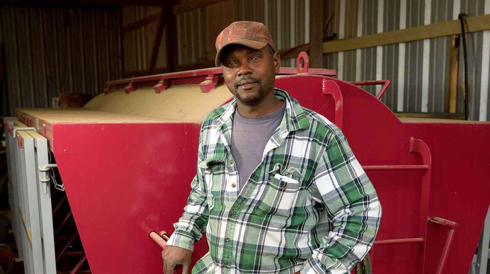 A man wearing a green and white plaid shirt, blue jeans, and a brown baseball cap stands in front of a bright red machine parked inside a metal building.
