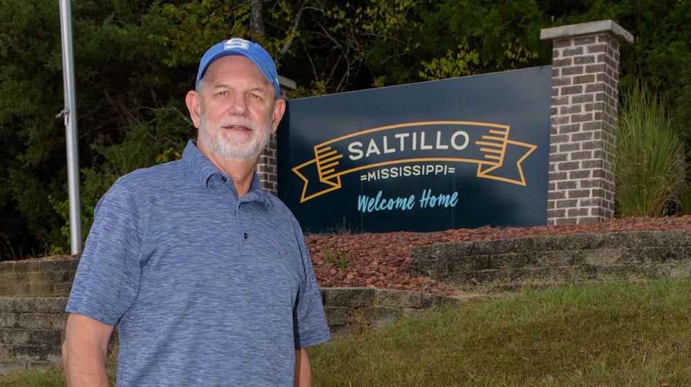 "A man stands in front of a sign that reads, ""Saltillo Mississippi, Welcome Home."""