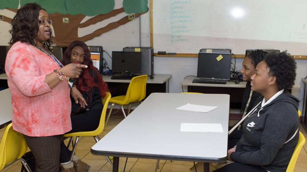 A woman, leftmost, wearing a coral blouse and brown slacks, points and talks to two teens sitting in yellow chairs at a gray table.