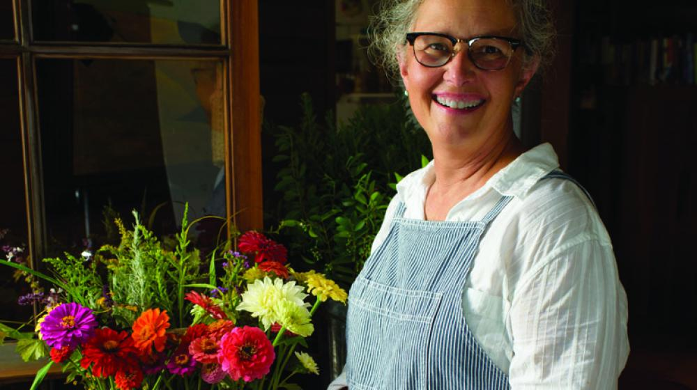 Woman with glasses stands smiling beside a flower arrangement