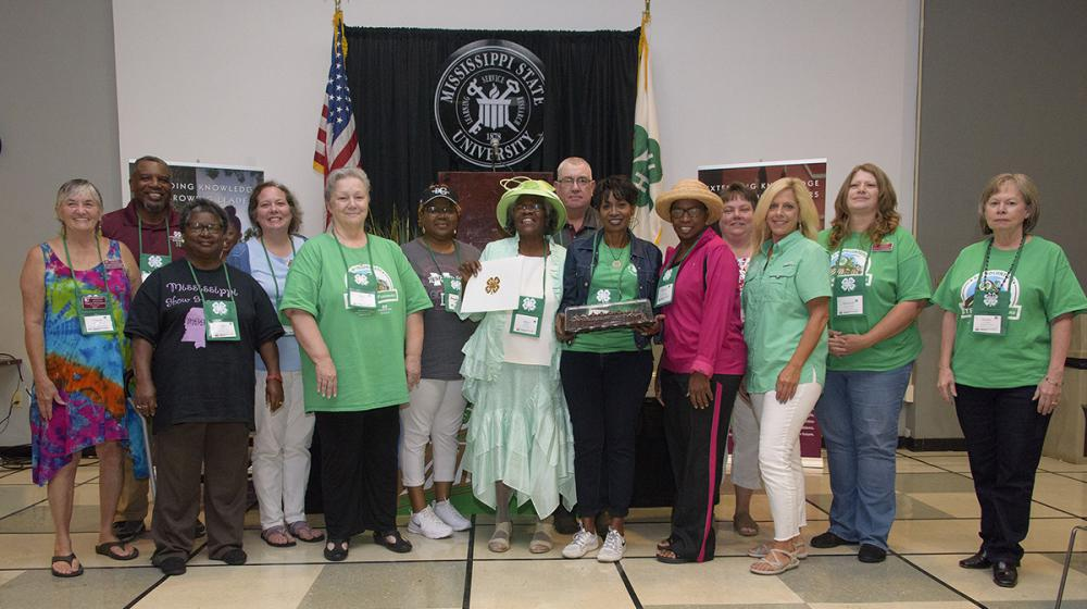 A group of 14 men and women stand on either side of a woman wearing a bright green hat and holding up an award.