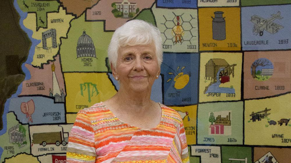 An elderly woman wearing an orange striped shirt stands in front of a large, multicolored, needlepoint county map of Mississippi.