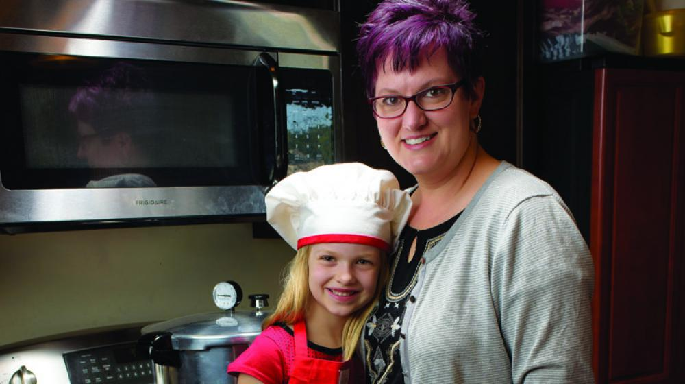 A little girl in a white chef's hat stands beside her mother
