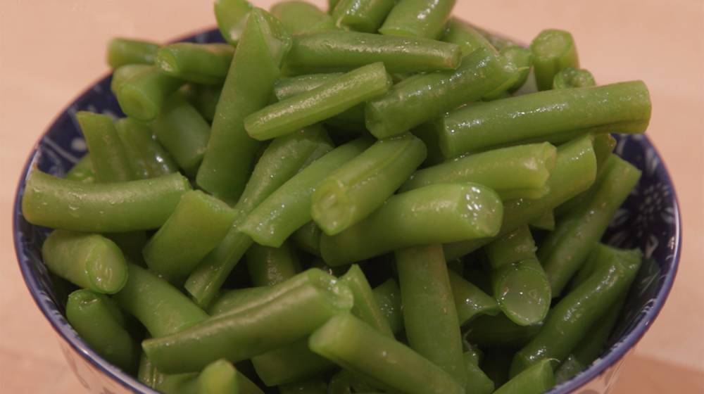 Freshly blanched green beans in a bowl.