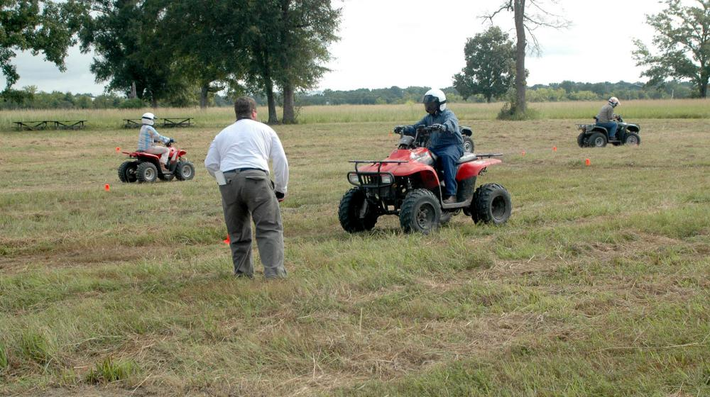 Three young people drive ATVs on a marked course in a field during a safety training.