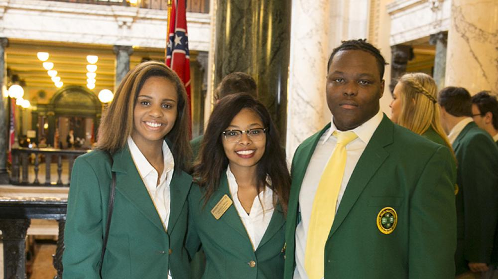 Two young women and one young man wearing green blazers stand on a marble floor.