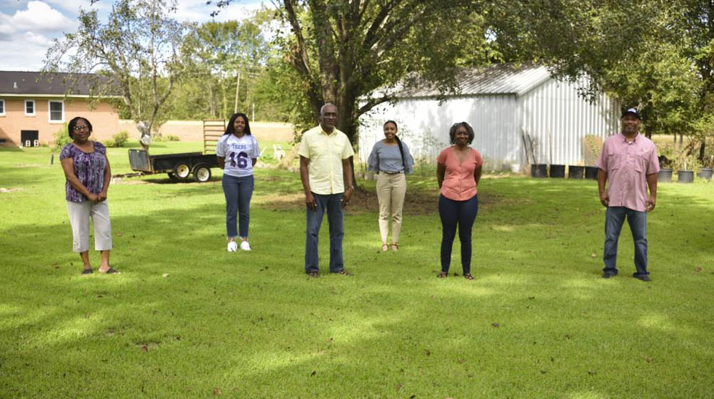 Four women and two men stand spaced out in green grass.