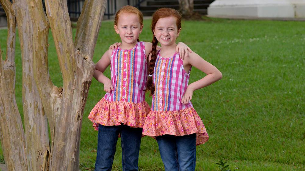 Two young girls with red hair and matching pink shirts stand next to each other with a hand on the hip.