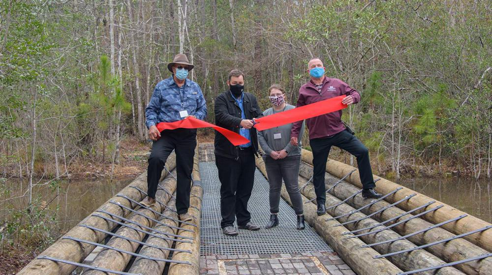 Four people stand behind a recently cut large red ribbon on a new bridge over a body of water.