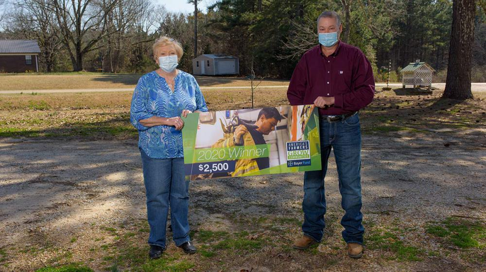 """A man and woman wearing masks hold each side of a banner that reads """"2020 Winner $2,500."""""""