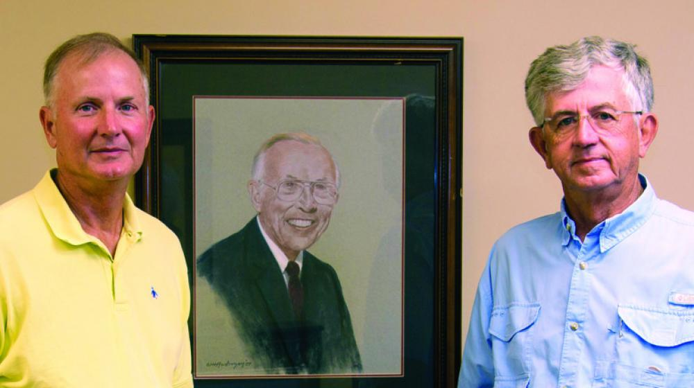 Two men, one in a yellow polo and the other in blue, stand in front of a portrait of a man