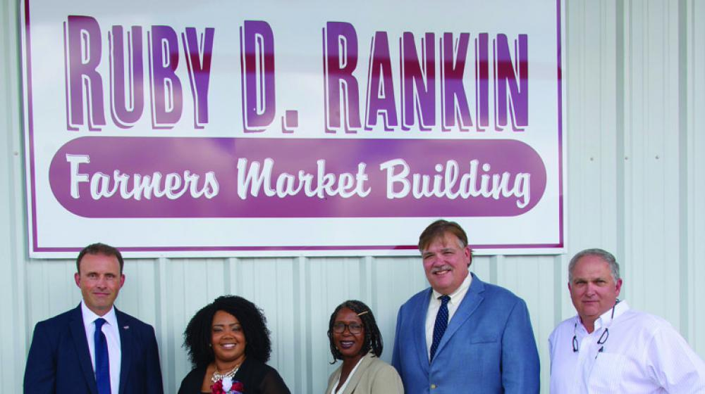 Five people, three men and two women, stand in front of a Farmers Market Building sign
