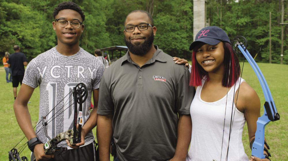 A 4-H volunteer leader with two 4-H members at a 4-H Shooting Sports event.