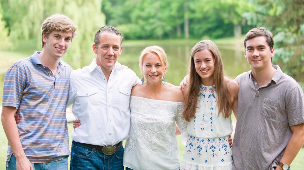Family photo of 2 parents and 3 young adults standing with arms around each other in front of a small body of water.