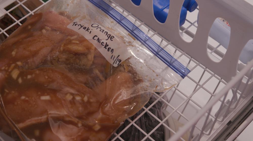 A labeled zip-top bag of Orange Teriyaki Chicken in the freezer.