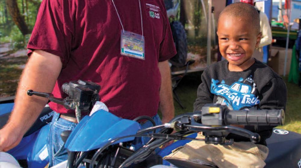 A man stands next to an ATV with a young boy sitting on the seat.