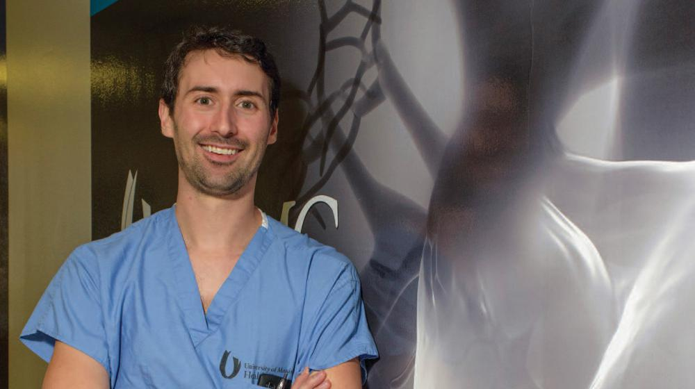 A man in blue scrubs with crossed arms leans against a wall.