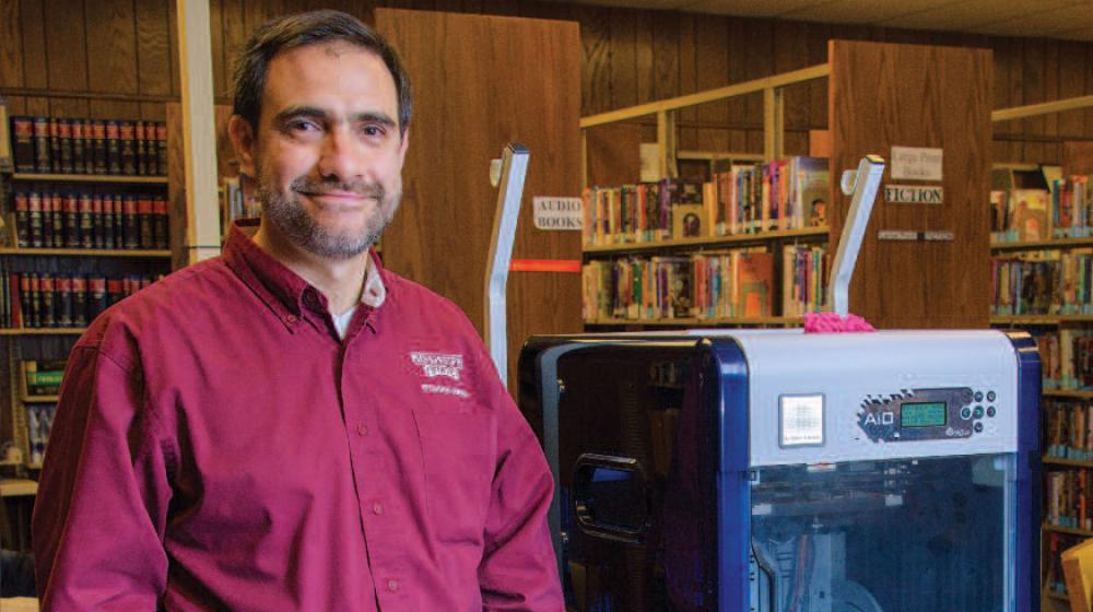 A man stands next to a 3D printer.