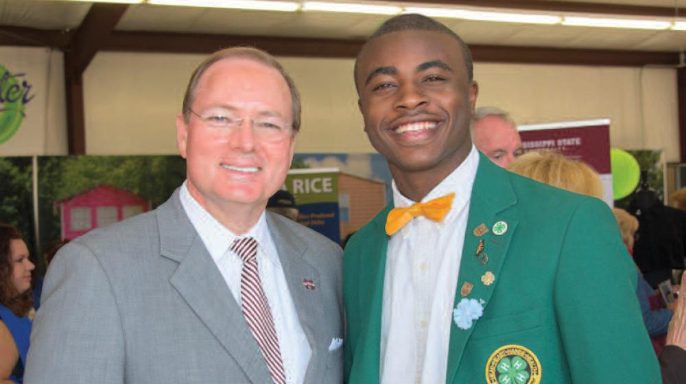MSU President Mark Keenum stands next to a young man in a green 4-H blazer.