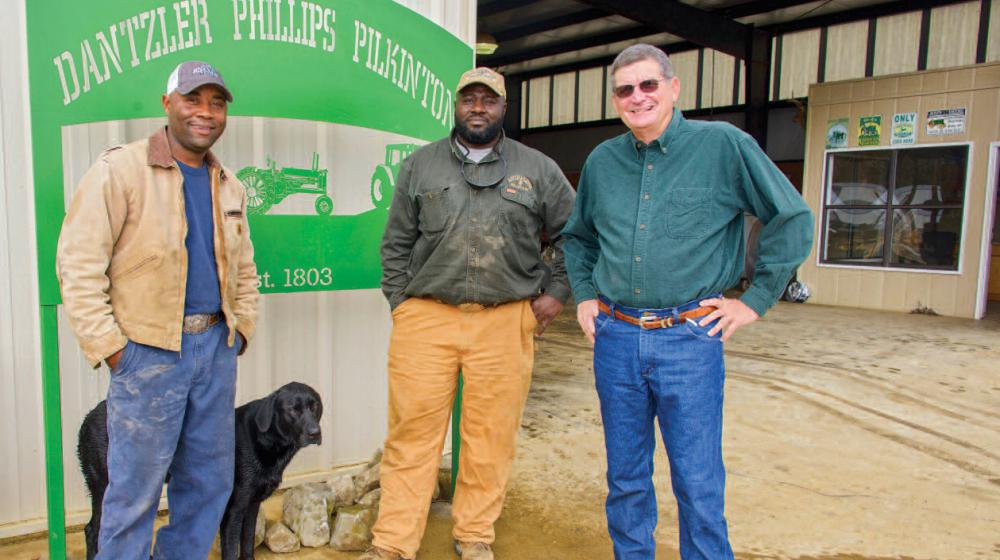 """Three men and a black dog stand in front of a sign that reads """"Dantzler Phillips Pilkinton."""""""