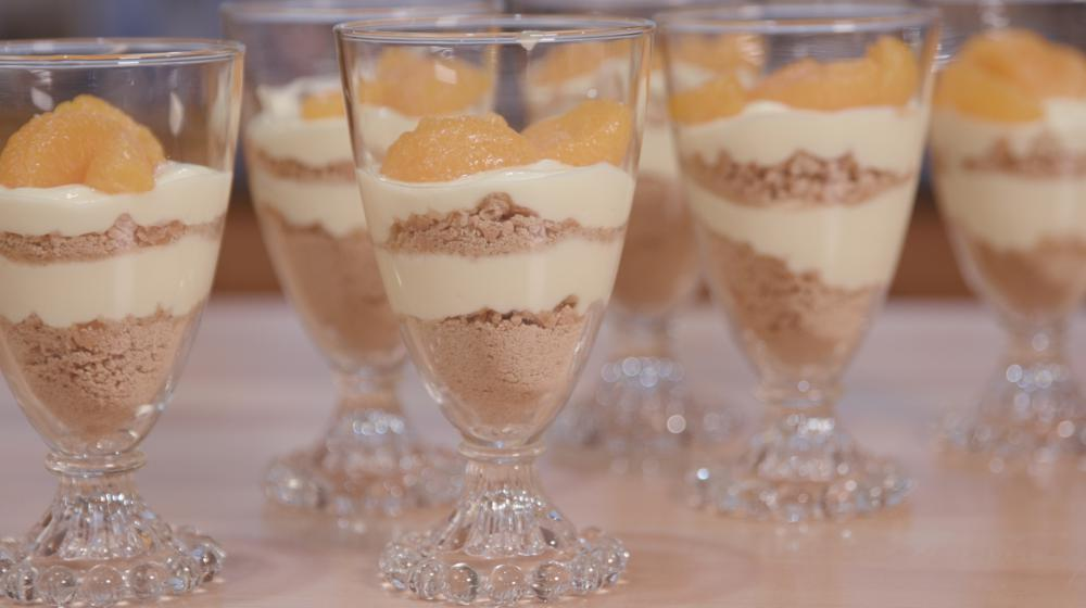 Clear glass parfait cups with lemon pudding layered with graham cracker crumbs topped with manadarin orange slices