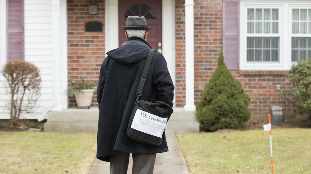 A census worker wearing a black hat and coat walking up to a house.