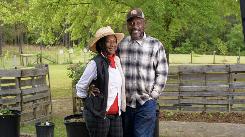A smiling couple standing next to each other in a garden.