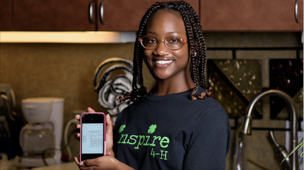 A smiling teenage girl stands behind a table covered in ingredients for a recipe displayed on a phone screen she holds in front of her.