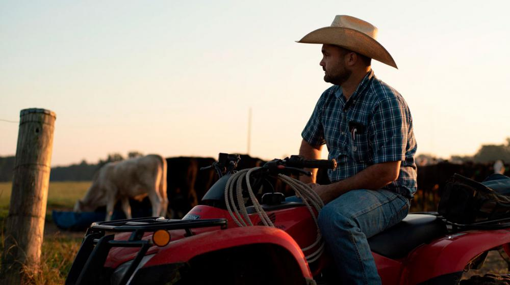 A man wearing a cowboy hat sits on an ATV in front of cows.