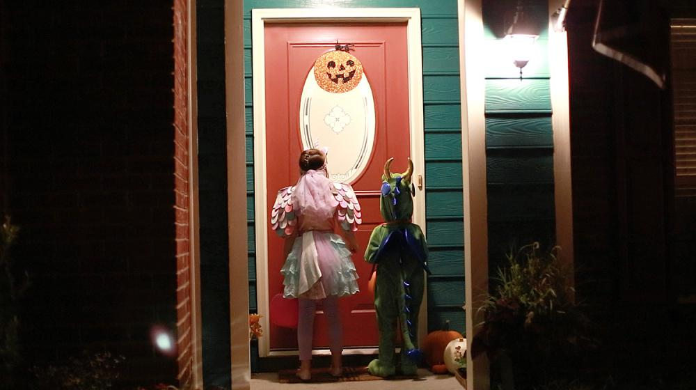 Two children waiting at a well-lit door for Halloween treats.