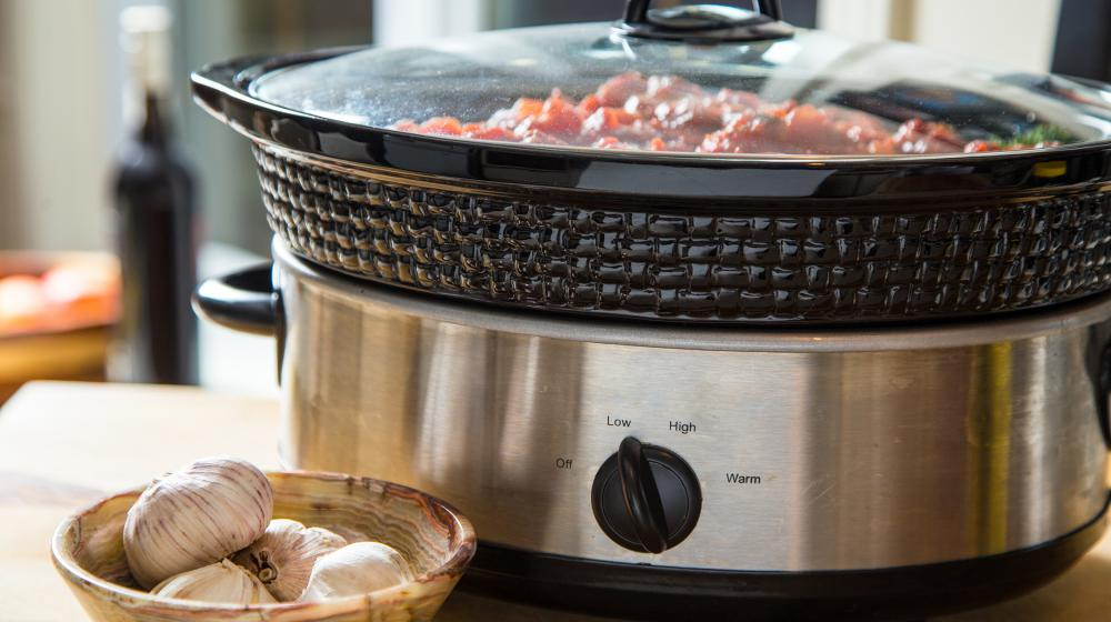 A slow cooker filled with a meal sits on a counter.