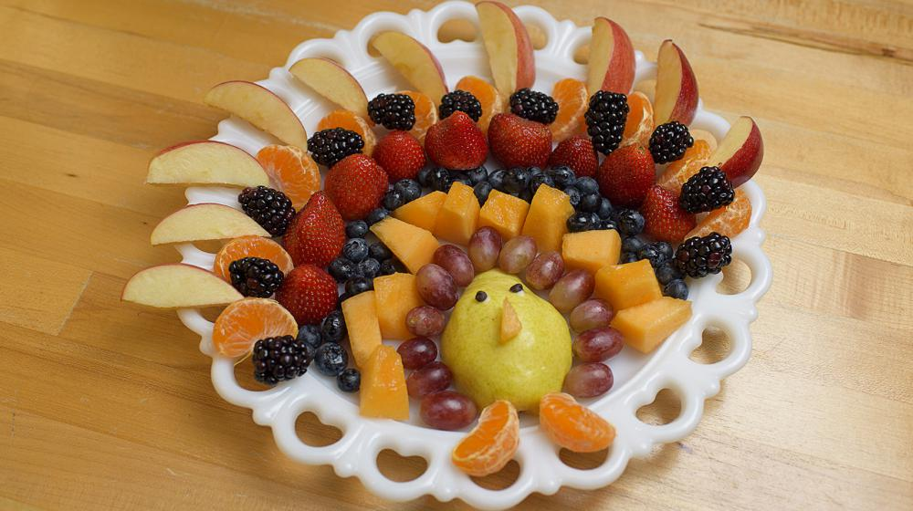 Several rows of fruit including apple slices, tangerine segments, blackberries, blueberries, cantaloupe, strawberries, grapes and a pear are arranged on a white platter in the shape of a turkey.