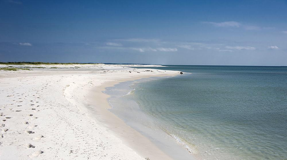 Dark blue water meets the edge of white sand on a clean, empty beach.