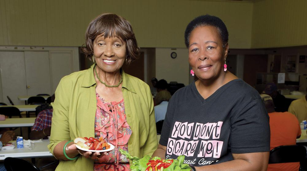 Two elderly women display their healthy food choices.