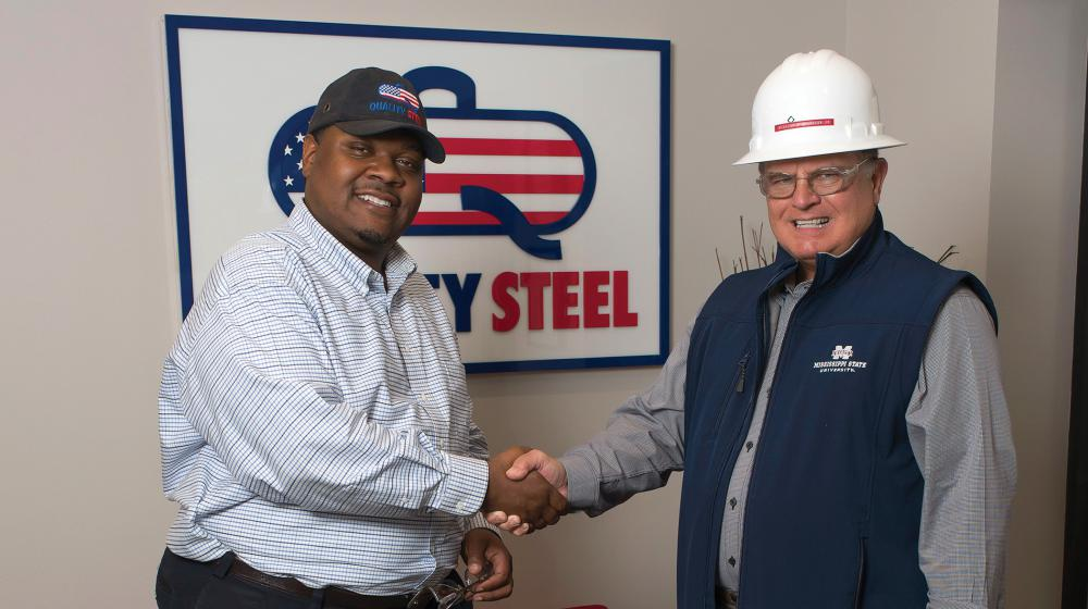 Two men shake hands in front of a Quality Steel sign.