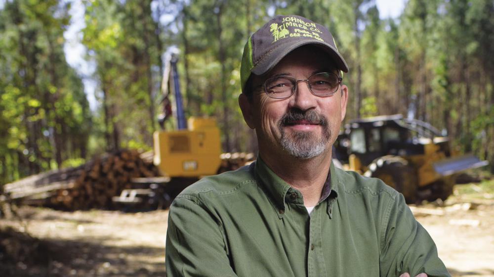 A man stands near a logging operation.