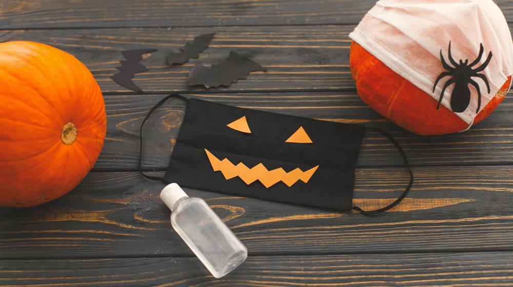 A black jack-o-lantern mask, bottle of sanitizer, and two pumpkins on a wooden backdrop.
