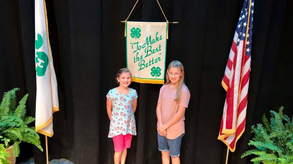"Two young girls stand in front of a sign that says ""To Make the Best Better!"" and between a 4-H flag and an American flag."