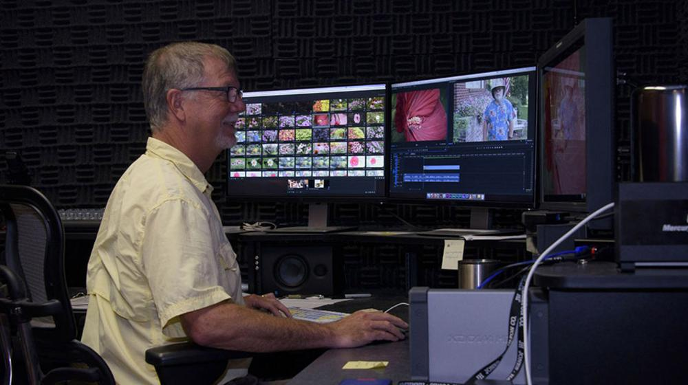 A man wearing a yellow shirt smiles at three video monitors.
