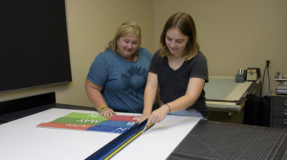 A woman with blonde hair and a blue shirt smiles as a younger brunette lady wearing a black shirt and measuring materials on a board.