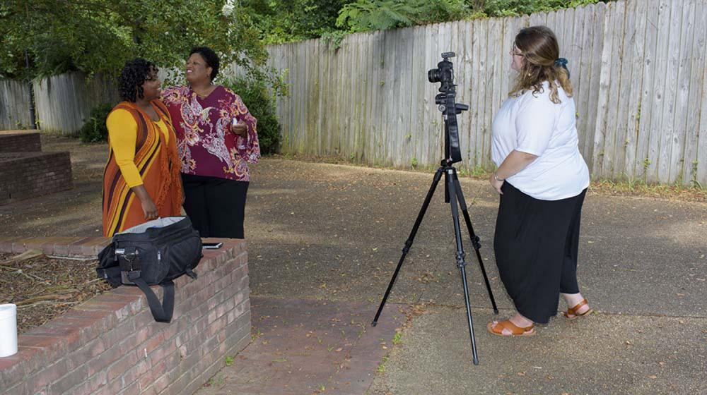 A woman wearing a white shirt stands behind a camera as two women in front of the camera smile.