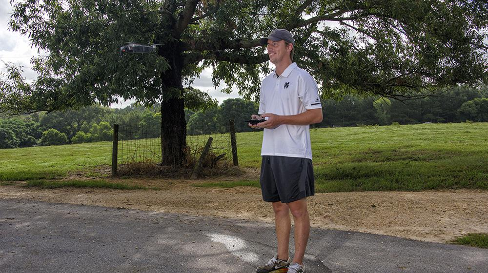 A man wearing a white shirt and blue baseball cap smiles as he looks at a drone flying through the air.
