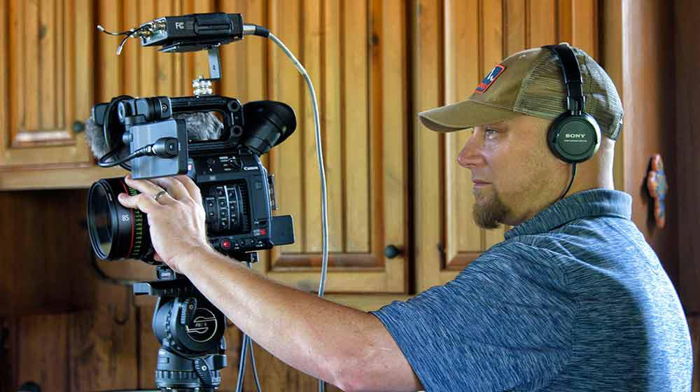 A man wearing a blue shirt and baseball cap adjusts a lens on a video camera.